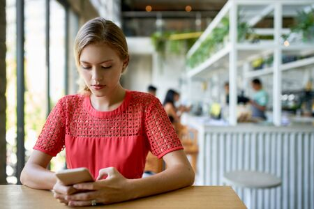 Lifestyle shot of young blonde caucasian natural millennial woman typing on cellphone at a modern tropical and bright restaurant with plants
