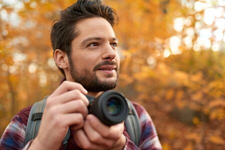 Attractive caucasian man taking pictures with a mirrorless camera through the forest in the fall in Canada 版權商用圖片