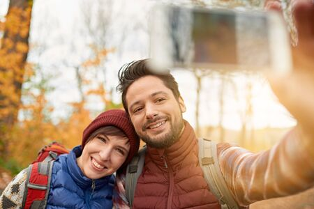 Couple of Canadian millennials taking selfies with a smartphone in a fall forrest