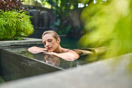Healthy woman relaxing outdoors in sunny and plant surrounded swimming pool of luxurious spa during tropical vacation in Bali