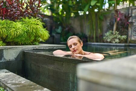 Pretty peaceful woman relaxing outdoors in sunny and plant surrounded swimming pool of luxurious hotel during tropical vacation in Bali