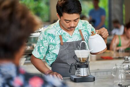 Candid lifestyle shot of smiling ethnic indonesian barista and small business owner preparing organic fair-trade coffee in bright trendy coffee shop wearing apron 版權商用圖片 - 128243083