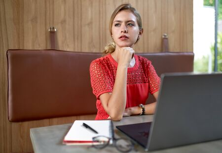 Closeup lifestyle portrait of young concentrated blonde caucasian millennial fashion designer working in a bright modern restaurant wearing bright clothing