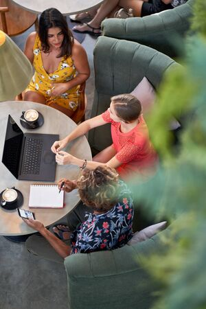Candid shot of three diverse millennial friends talking over coffee with laptop computer at bright cafe serving fair-trade coffee