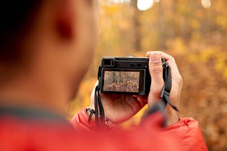 Attractive indian man taking pictures with a mirrorless camera through the forest in the fall in Canada 版權商用圖片