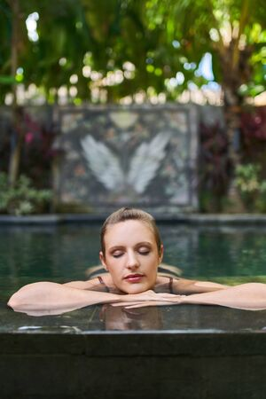 Beautiful zen woman relaxing outdoors in lush and modern stone swimming pool of luxurious hotel during tropical travel in Bali 版權商用圖片