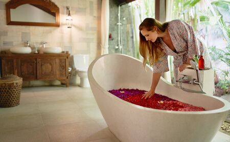 Pretty natural female touching flower petals floating in luxurious bathtub of tropical spa and wellness centre