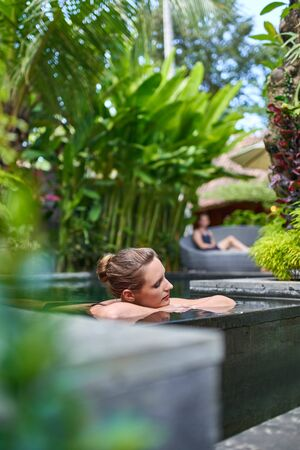 Pretty peaceful woman relaxing outdoors in sunny and lush stone swimming pool of luxurious hotel during tropical holiday in Bali 版權商用圖片 - 128243127