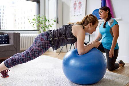 Entrenador personal de mujer china durante una sesión de entrenamiento con un atractivo cliente rubio en un consultorio médico brillante Foto de archivo