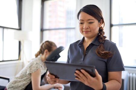 portrait of a Chinese woman massage therapist holding a tablet while filling the file of an attractive blond client at her workplace in a bright office