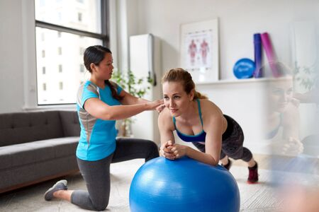 Chinese woman personal trainer during a workout session with an attractive blond client in a bright medical office 版權商用圖片