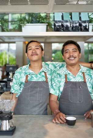 Lifestyle portrait of two smiling millennial balinese coworkers wearing trendy clothing in bright hipster cafe and restaurant serving fair-trade coffee 版權商用圖片