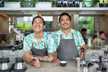 Lifestyle portrait of two friendly smiling balinese millennial baristas wearing trendy clothing and aprons in hipster cafe serving fair-trade coffee