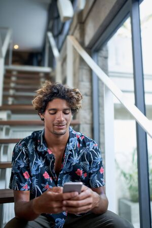 Attractive ethnic hipster millennial business man smiling and reading blog cellphone sitting on modern stairs of bright room with tropical plants