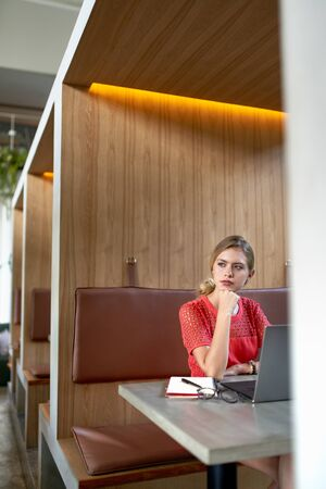 Closeup lifestyle portrait of beaufitul focused blonde caucasian millennial freelancer working at large wooden table of a trendy modern cafe