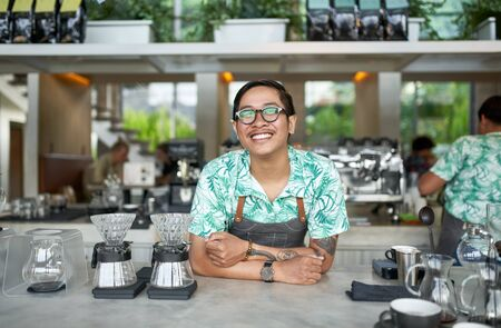 Lifestyle portrait of smiling balinese millennial barista wearing glasses, mustache and trendy clothing in bright hipster cafe serving fair-trade coffee
