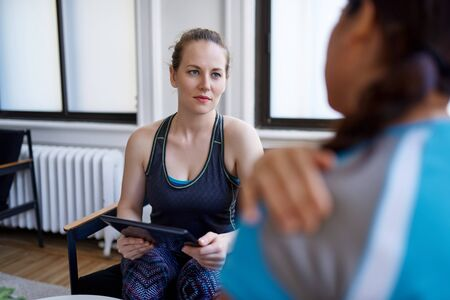 Caucasian woman physiotherapist talking to a mid-adult chinese female patient and taking notes on a tablet during a fitness evaluation consultation 版權商用圖片