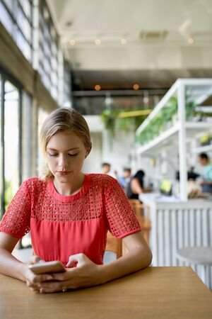 Lifestyle shot of young blonde caucasian natural millennial woman looking at cellphone at a modern tropical and bright restaurant with plants