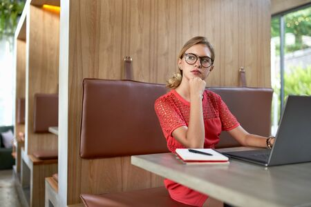 Closeup lifestyle portrait of pensive blonde caucasian millennial vlogger in her 20s wearing glasses working on laptop in a modern restaurant