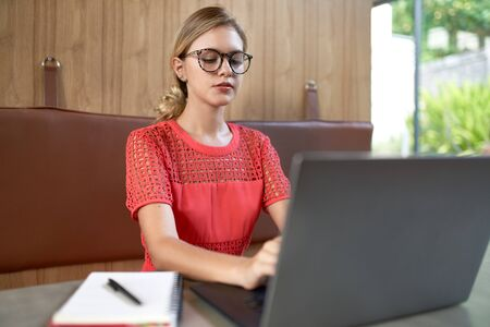 Closeup lifestyle portrait of professional blonde caucasian millennial student wearing glasses taking notes on laptop computer in a modern restaurant 版權商用圖片