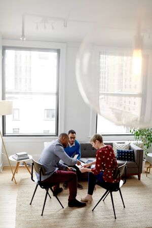 Multi-ethnic team of creative millenials collaborating on a brainstorm project Stock Photo