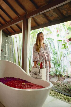 Pretty caucasian girl relaxing outside large bath tub filled with organic flower petals in tropical therapy and wellness centre