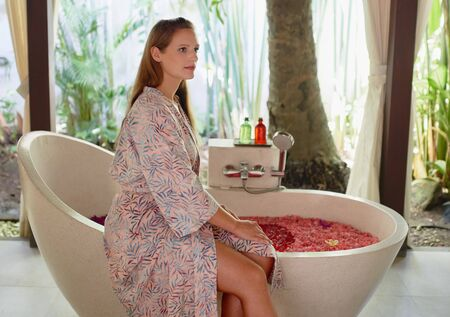 Closeup of gorgeous caucasian millennial woman relaxing at tropical hotel spa with serene herbal bath and flower treatment in Bali