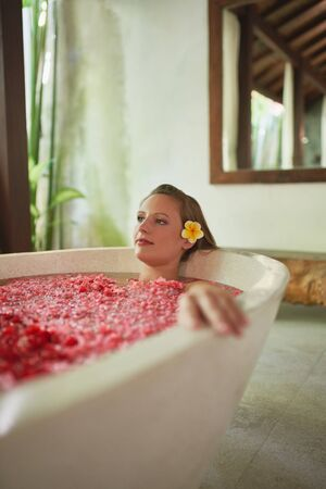 Pretty white female with yellow flower accessory relaxing in warm bathtub filled with rose petals in tropical resort and spa