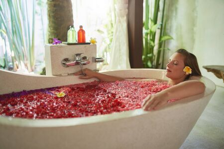 Natural millennial woman being pampered in luxurious white bathtub filled with flower petals in tropical resort and wellness centre