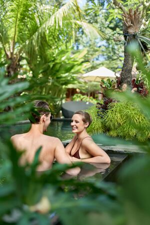 Candid shot of two happy people relaxing together in lush resort pool of luxurious hotel in tropical Bali during retreat