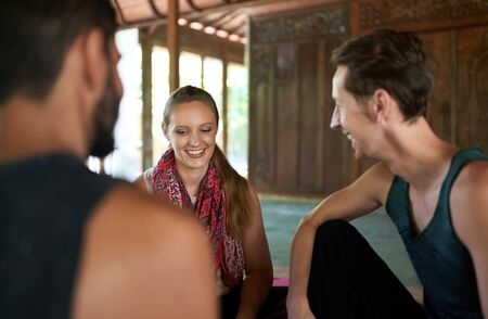 Candid shot of three diverse friends discussing together after yoga class in traditional temple in Bali, Indonesia 版權商用圖片