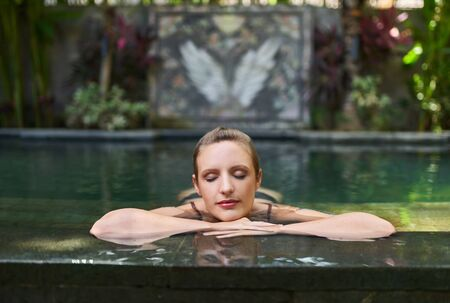Beautiful real woman relaxing outdoors in lush and exotic stone swimming pool of luxurious resort during tropical vacation in Bali 版權商用圖片