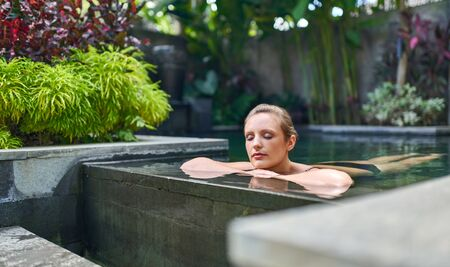 Beautiful peaceful woman relaxing outdoors in sunny and lush stone swimming pool of luxurious hotel during tropical vacation in Bali