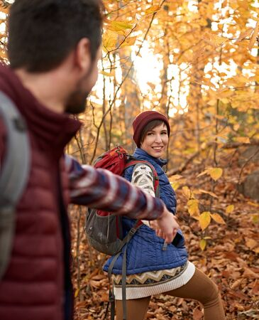 POV picture of an attractive caucasian couple hiking through the forest in the fall in Canada