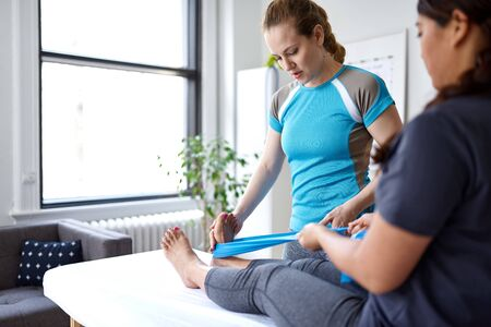 Caucasian woman physiotherapist strectching the leg and knee of a mid-adult chinese female patient sitting on a massage table