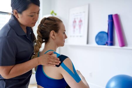 Chinese woman massage therapist applying kinesio tape to the shoulders and neck of an attractive blond client in a bright medical office 版權商用圖片