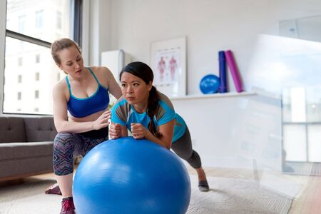 Caucasian woman physiotherapist giving a workout session to a mid-adult chinese female patient on a stability ball