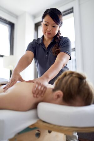 Chinese woman massage therapist giving a treatment to an attractive blond client on massage table in a bright medical office