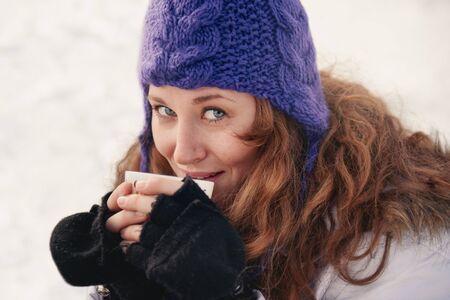 Solo woman enjoying cocoa in the snow in winter
