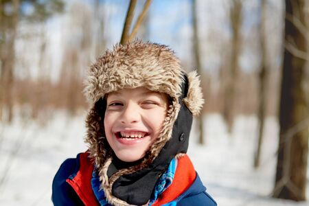 Portrait of a smiling boy enjoying playing in fresh snow during wintertime and wearing a fur trimmed hat