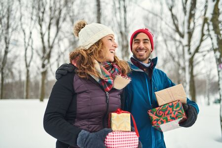 Smiling diverse couple holding Christmas presents while walking through a winter forest 版權商用圖片