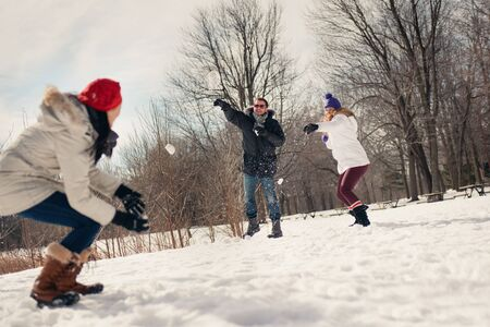 Group of millenial young adult friends throwing snowballs in wintertime in a snow filled park