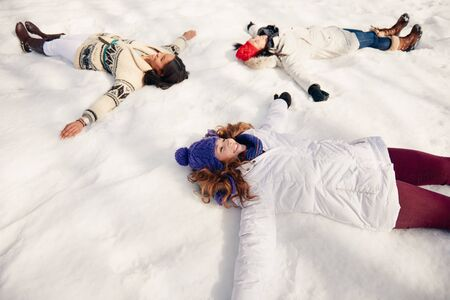 Group of girl friends making snow angels in winter