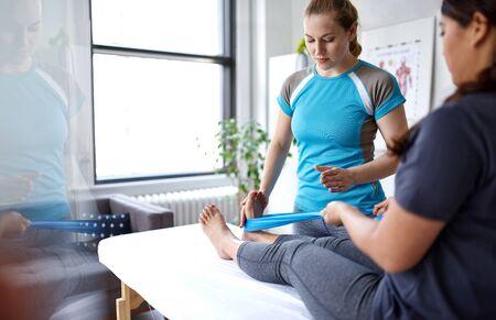 Kaukaski fizjoterapeuta rozciągający nogę i kolano
