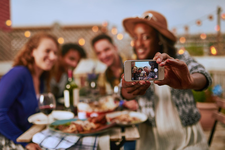 Group of diverse friends taking selfies pictures having dinner a