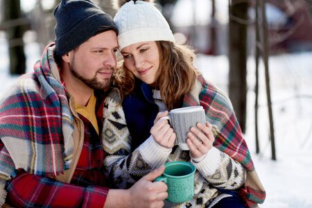 Couple in love enjoying a tender moment in fresh snow during wintertime and drinking hot chocolate together