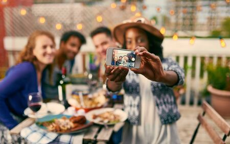 Group of diverse friends taking selfies pictures having dinner al fresco in urban setting Stock Photo