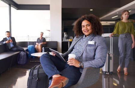 African american man waiting for flight sitting in modern airport lounge on tablet with luggage