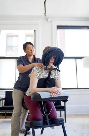 Chinese woman massage therapist giving a neck and back pressure Archivio Fotografico