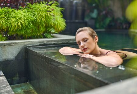 Healthy woman relaxing outdoors in sunny and plant surrounded swimming pool of luxurious resort during tropical vacation in Bali Фото со стока